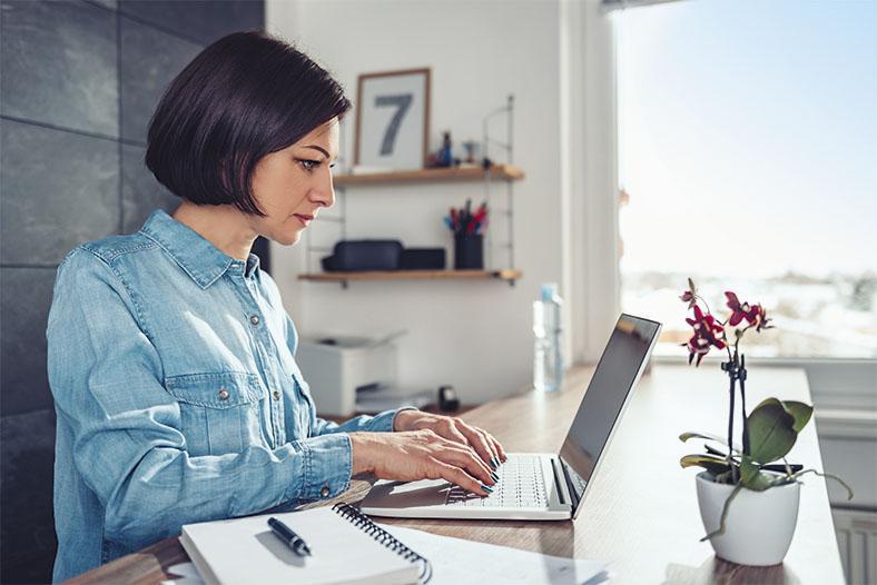 Das Foto zeigt eine Frau im Profil mit dunklem Pagenschnitt und blauer Bluse. Sie sitzt an zuhause an einem Schreibtisch und tippt auf einer Laptop-Tastatur, rechts im Bild steht eine blühende Topfpflanze auf dem Tisch. Im Hintergrund sieht man ein Wandregal und ein Fenster mit Blick auf blauen Himmel.