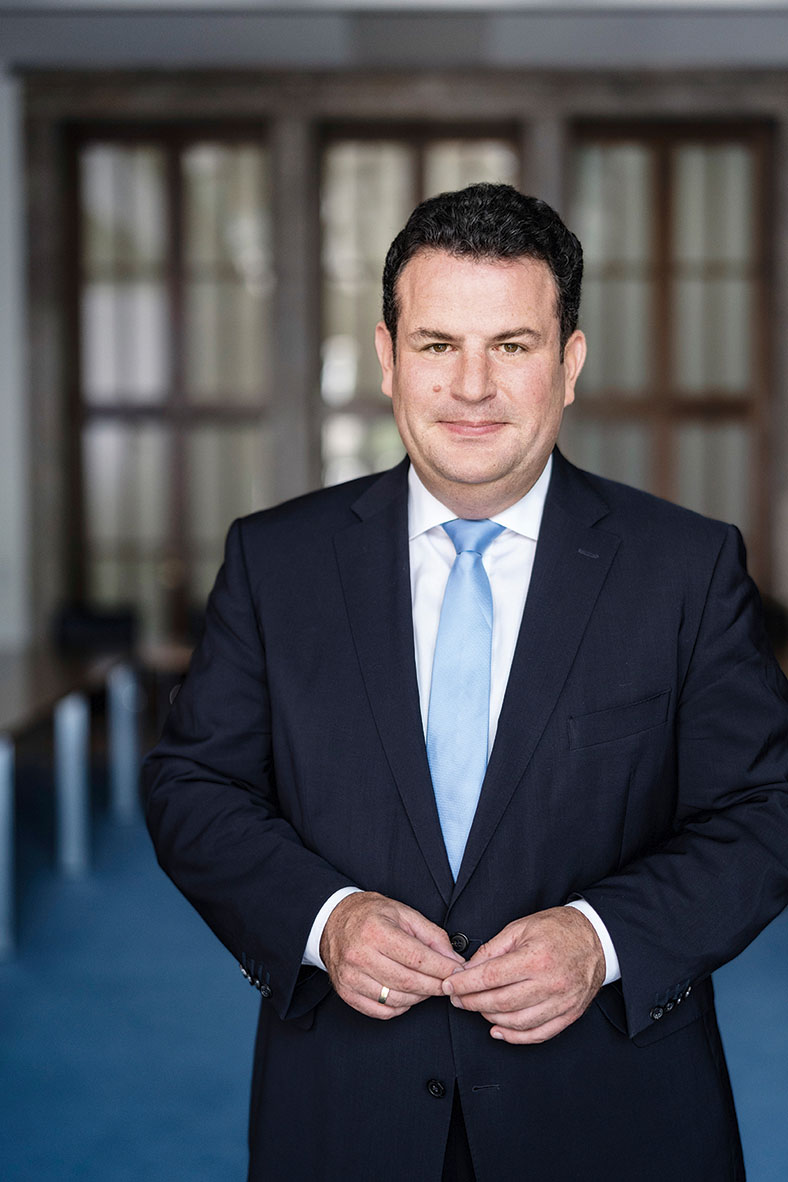 Porträt von Bundesarbeitsminister Hubertus Heil. Er trägt kurze dunkle Haare und einen dunklen Anzug mit weißem Hemd und hellblauer Krawatte.