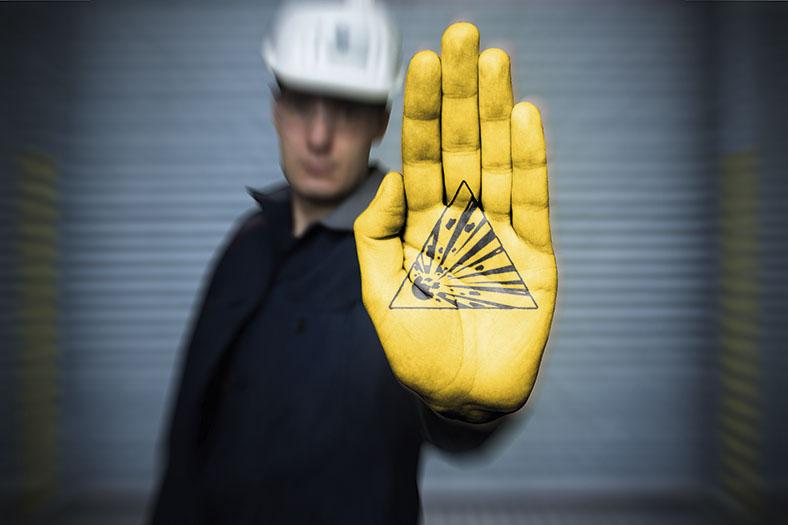 Das Bild zeigt im Hintergrund unscharf einen Mann in dunkler Kleidung mit hellem Schutzhelm. Er hält eine gelbliche Handfläche in den Vordergrund, auf der man das dreieckige Piktogramm für Explosionsgefahr in schwarz sieht.