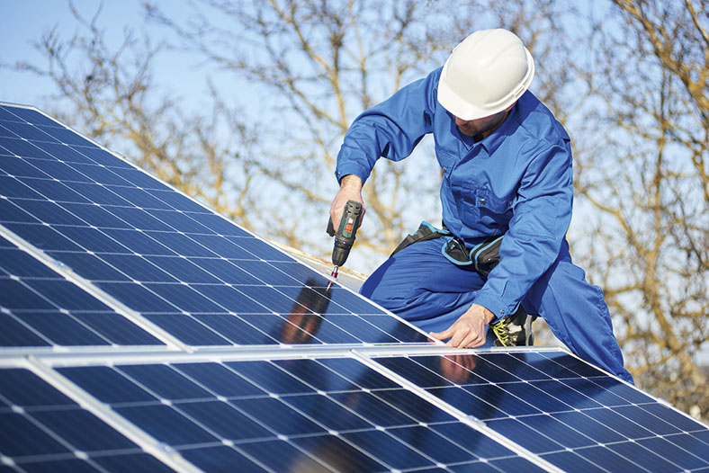 Auf dem Foto sieht man einen Arbeiter in Blaumann und weißem Schutzhelm auf einem Dach. Er montiert Solarzellen mit einem Akkuschrauber. Im Hintergrund Äste eines Baumes und blauer Himmel.