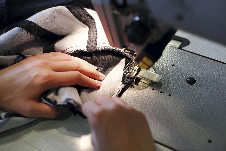Blick von oben auf eine Nähmaschine mit Fingerabweiser. Zwei Frauenhände halten ein Kleidungsstück in Position beim Nähvorgang.