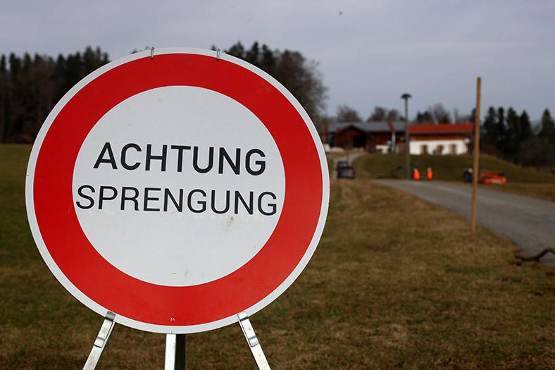 """Rundes Hinweisschild """"Achtung Sprengung"""", im Hintergrund Landschaft mit Freileitungsmast."""