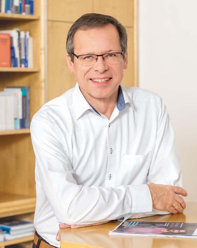 Porträtfoto von Johannes Tichi, Vorsitzender der Geschäftsführung der BG ETEM. Er hat kurze Haare und eine Brille. Er trägt ein helles Hemd und stützt beide Arme auf einen Stehtisch, auf der die neue Ausgabe des etem-Magazins liegt.
