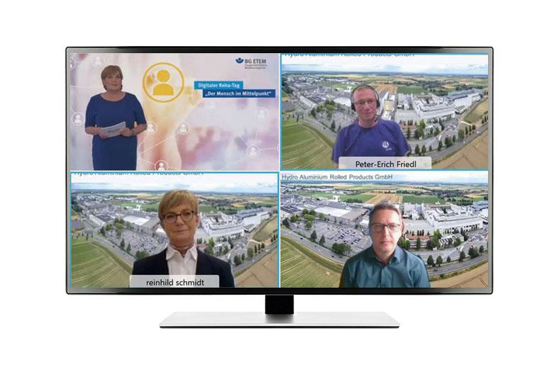 Virtuelle Verleihung des Rehabilitationspreises der BG ETEM: Ein Großbildschirm zeigt vier Bildausschnitte mit je einer Person. Bei drei Ausschnitten ist im Hintergrund eine Fabrikanlage aus der Vogelperspektive zu sehen, im linken oberen Ausschnitt eine Präsentationsleinwand mit einer davorstehenden Moderatorin in einem blaue Kleid.