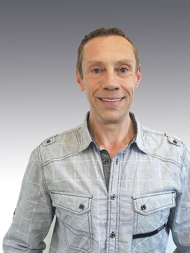 Porträt von Wolfgang Volkamer, Vertriebsleiter KDSL GmbH in Germering. Herr Volkamer hat kurze hellbraune Haare, er trägt ein graues Hemd und lächelt in die Kamera.