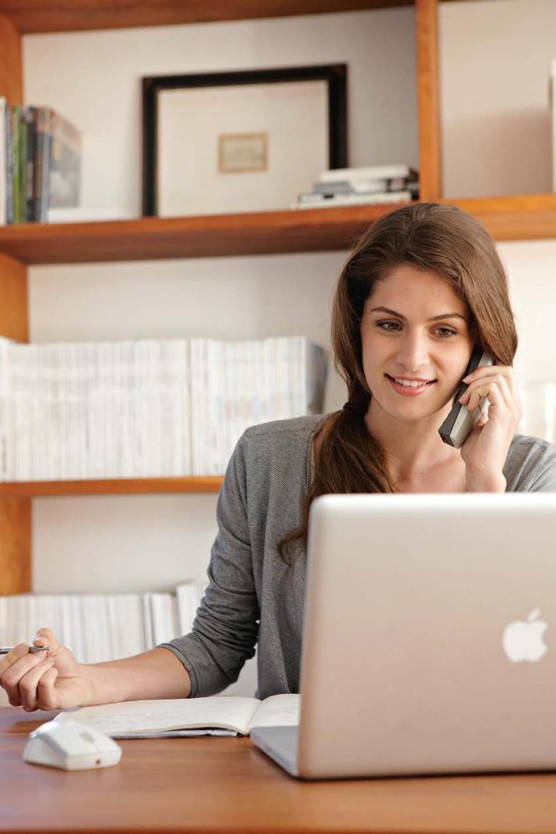 Junge Frau mit dunklen langen Haaren in einer grauen Jacke sitzt vor ihrem Notebook im Homeoffice und telefoniert, im Hintergrund ein Bücherregal.
