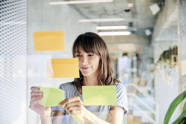Frau im mittleren Alter mit halblangen braunen Haaren in kurzärmeligem grauen T-Shirt klebt farbige Zettel an eine Scheibe als Maßnahme zum Zeitmanagement.