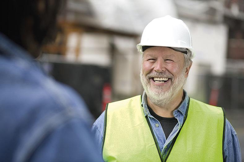 Betriebsbesichtigung für Gefährdungsbeurteilung: Brustbild eines lachenden älteren Mannes mit weißem Vollbart. Er trägt einen weißen Bauhelm, ein Jeanshemd und eine gelbe Sicherheitsweste.