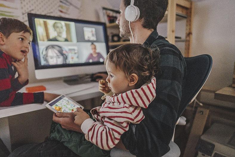 Vater mit zwei kleinen Kindern sitzt mit Kopfhörer im Homeoffice am PC und nimmt an einer Videokonferenz teil. Eins der Kinder sitzt auf seinem Schoß und schaut auf ein Tablet, das andere lehnt sich auf den Schreibtisch und schaut dem Vater zu.Vater mit zwei kleinen Kindern sitzt mit Kopfhörer im Homeoffice am PC und nimmt an einer Videokonferenz teil. Eins der Kinder sitzt auf seinem Schoß und schaut auf ein Tablet, das andere lehnt sich auf den Schreibtisch und schaut dem Vater zu.