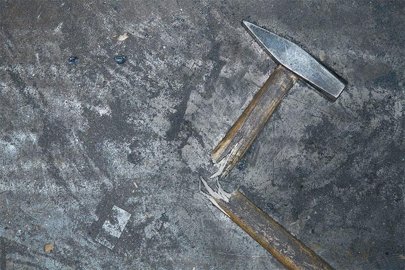 Motiv Arbeitsunfall: Ein Hammer mit zerbrochenem Holzstiel liegt auf einem grauen Untergrund.