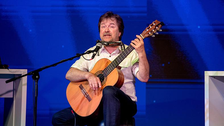 Mario Fritzsche von der Ontex GmbH sitzt auf einem Hocker mit einer Gitarre und spielt.