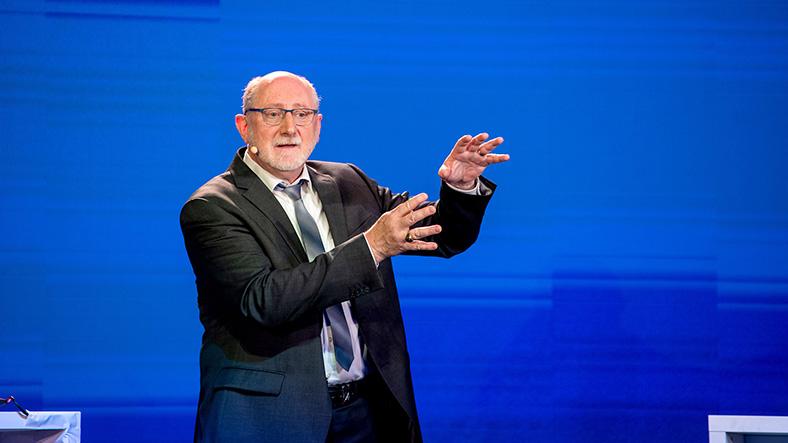 Dr. Ronald Unger, langjährige Aussichtsperson der BG ETEM und Referent für Sicherheitswerbung, steht im Anzug auf einer Bühne mit blauem Hintergrund.
