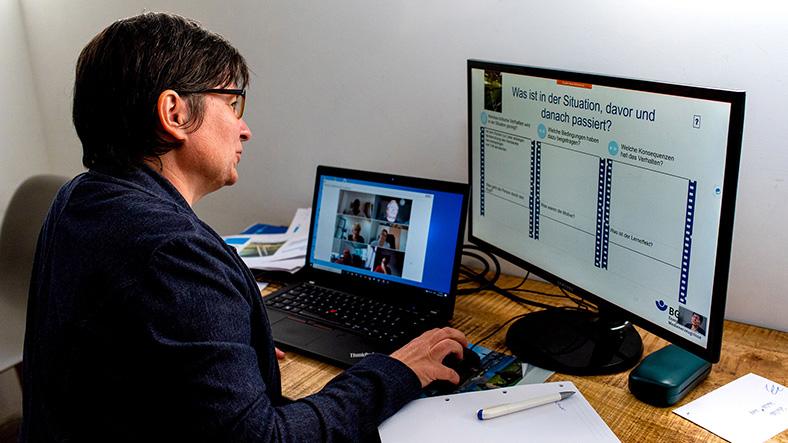 Mitarbeiterin am PC in Videokonferenz mit weiteren Personen, die auf einem Notebook-Bildschirm sichtbar sind. Daneben ein großer Monitor mit Daten zur Arbeitssicherheit.