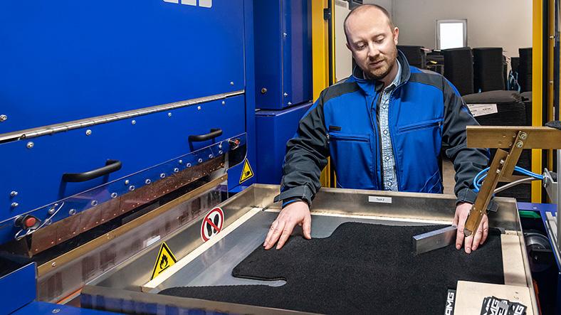 Qualitätskontrolle von Fußmatten: Ein Mitarbeiter begutachtet eine fertig genähte Auto-Fußmatte.