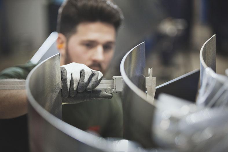 Im Vordergrund erkennt man einen Handschuh, der ein scharfkantiges Metallteil behandelt. Dies ist ein spezieller Handschuh gegen Schnittverletzungen. Im Hintergrund sieht man schemenhaft das Gesicht des Facharbeiters.