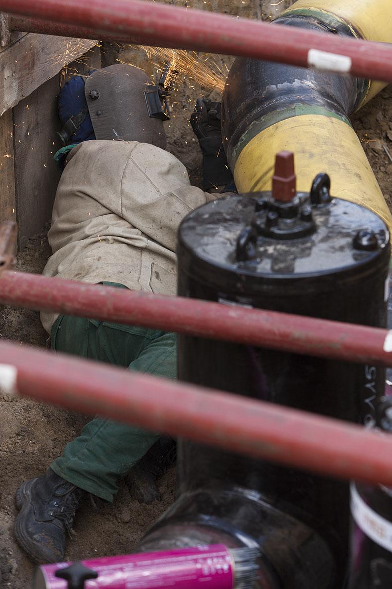 Diese Abbildung zeigt einen Schweißer liegend neben einem Rohr arbeiten.