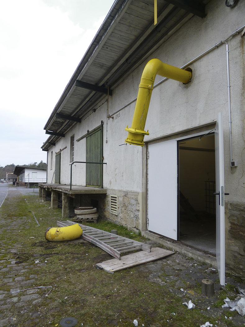 Dieses Foto zeigt ein gelbes abgewinkeltes Rohr. Ein abgebrochenes Teil Rohr liegt auf dem Boden.