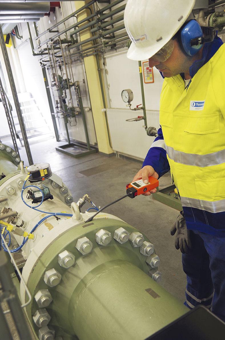Ein Facharbeiter mit Schutzausrüstung überprüft mit einem Messgerät die Gaskonzentration an einer Gasanlage.