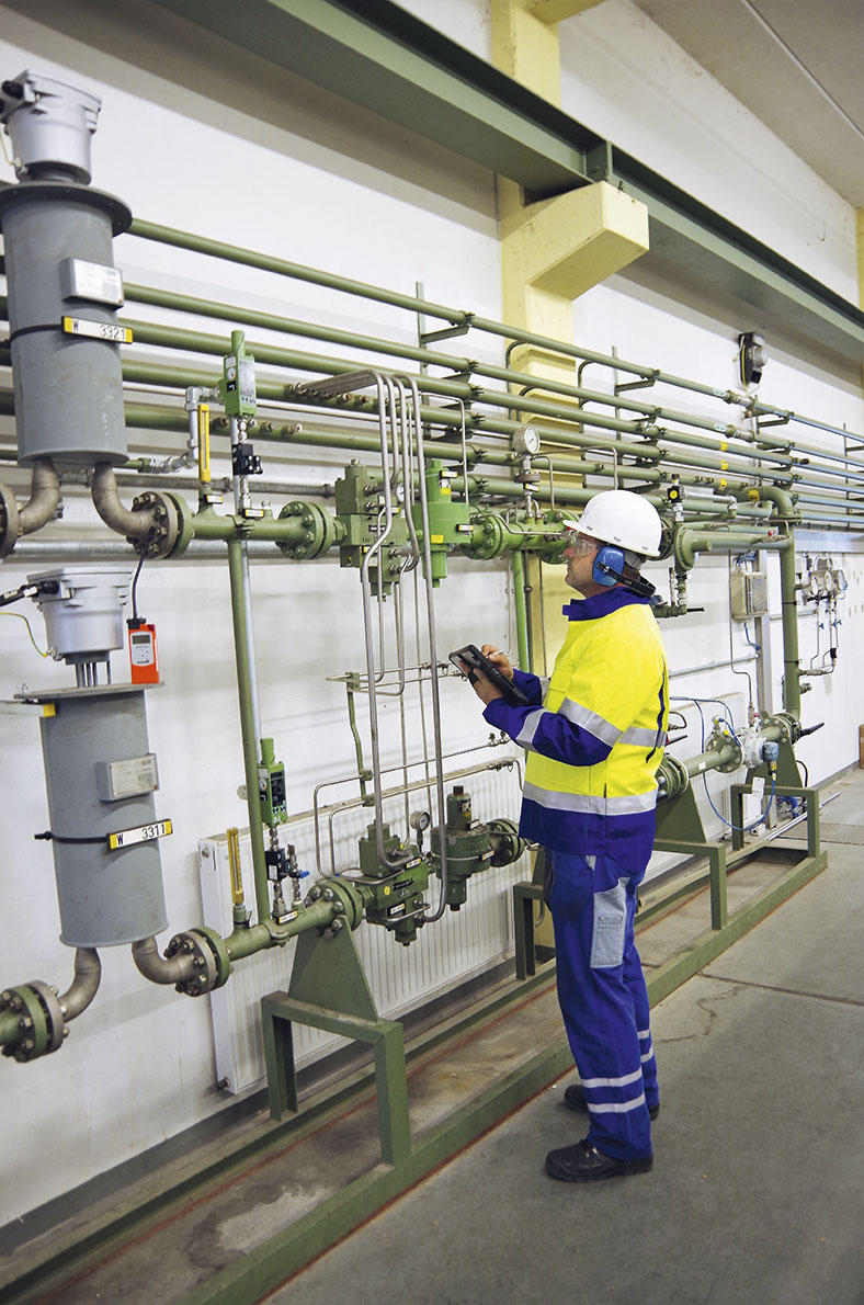 Das Foto zeigt einen Facharbeiter mit entsprechender persönlicher Schutzausrüstung. Er begutachtet eine vor ihm befindliche Gasanlage.