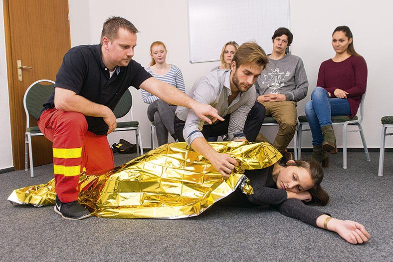 Ein Ausbilder eines Rettungsdienstes leitet einen Mann während eines Ersthelfer-Seminars an. Der Seminarteilnehmer legt eine Kälteschutzdecke über eine am Boden liegende Frau. Im Hintergrund sitzen Seminarteilnehmer.