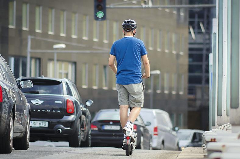 Das Foto zeigt einen Mann von hinten, der mit einem E-Scooter unterwegs ist. Er trägt einen Fahrradhelm.