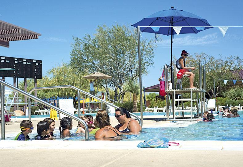 Dieses Foto zeigt einen Teil von einem Schwimmbecken. Unter einem Sonnenschirm sitzt die Badeaufsicht. Im Vordergrund sind ein paar Personen im Schwimmbecken zu sehen.