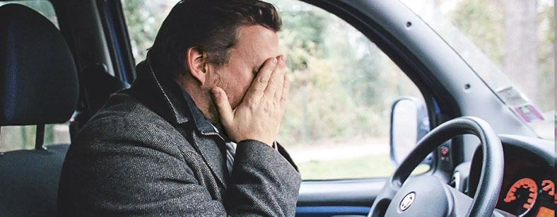 Das Foto zeigt einen Mann, der im Auto sitzt und die Hände vor das Gesicht hält.