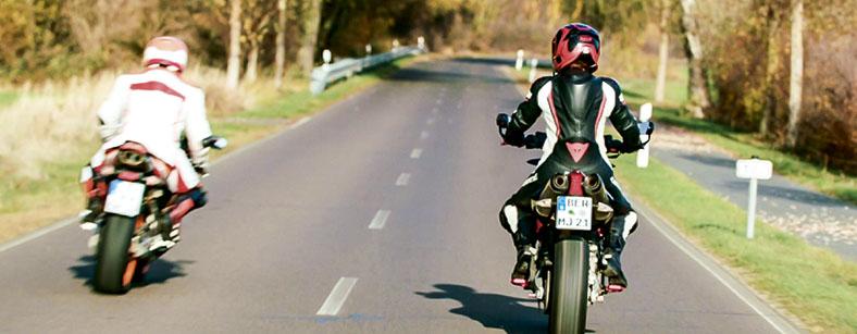 Ein Motorradfahrer überholt gerade einen anderen Motorradfahrer auf einer Landstraße.