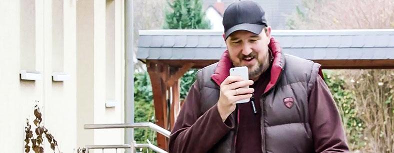 Dieses Bild zeigt einen Mann, der eine Audionachricht aufs Handy spricht.