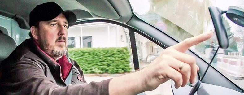 Das Foto zeigt einen Mann, der in einem Auto sitzt und mit der rechten Hand das Navigationsgerät einstellt.