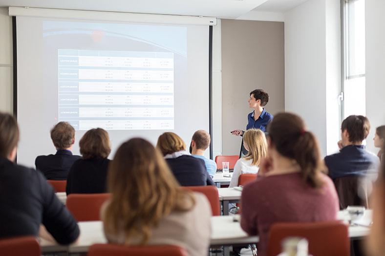 Dieses Foto zeigt Personen von hinten, die an einem Laserschutzbeauftragten-Lehrgang teilnehmen. Im Vordergrund erkennt man eine Seminarleiterin, die per Fernbedienung die Präsentation navigiert.