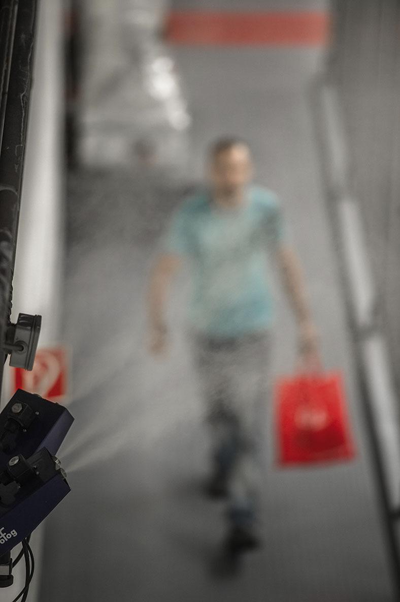 """Dieses Bild zeigt schemenheft einen Mann, der etwas mit der linken Hand trägt. Das Bild ist durch eine beschlagene Scheibe aufgenommen worden. Es geht um das Thema """"Wasserqualität bei Luftbefeuchtern""""."""