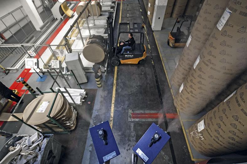 Das Foto zeigt ein Papierlager. In Regalen lagert Papier und Pappe. Ein Stapelfahrer steht mit seinem Wagen vor einem Regal. In der Mitte stehen einige Maschinen. Auf der rechten Seite im Vordergrund stehen große Rollen, die verpackt sind.