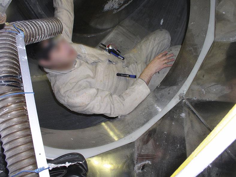 Das Foto zeigt einen Facharbeiter fast liegend in einer Waschröhre. Über ihm der Auslass des Belüftungsschlauchs.