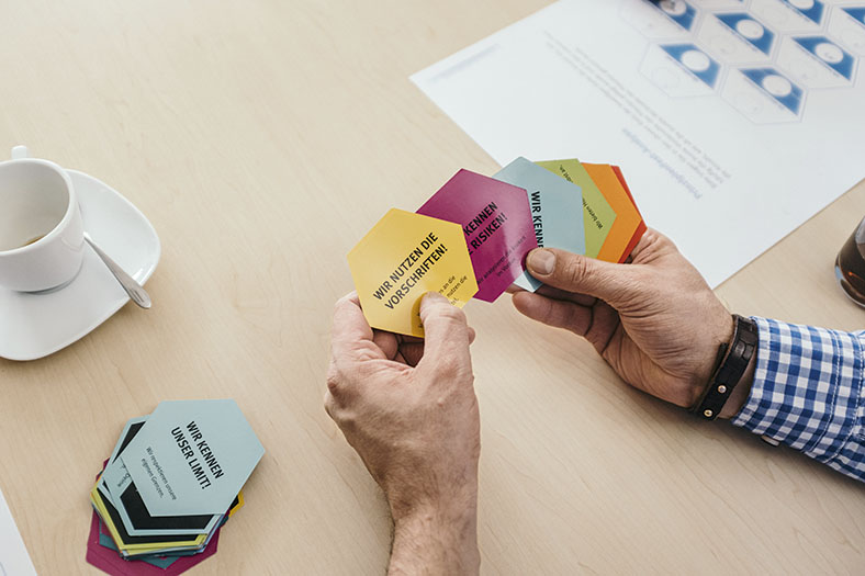 Auf diesem Foto halten Hände die farbigen Spielekärtchen eines Spiels zum Thema Prävention und Arbeitssicherheit fest.