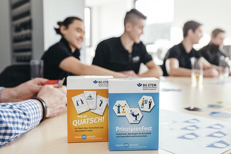 """Das Foto zeigt zwei Schachteln mit den Spielkarten-Sets """"Prinzipienfest"""" und """"Das ist Quatsch"""". Im Hintergrund erkennt man schemenhaft die Azubis, die an einem Tisch sitzen."""