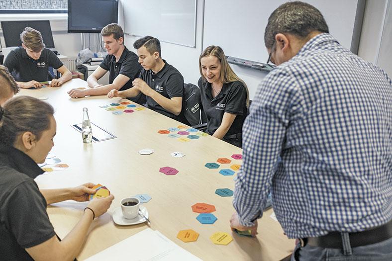 """Hier sitzen die Azubis an einem Tisch. Im Vordergrund die """"Sifa"""" (Sicherheitsfachkraft). Auf dem Tisch die Spielekärtchen. Es geht um spielerische Prävention in der Ausbildung zum Thema """"Arbeitssicherheit""""."""