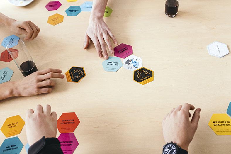 Das Foto zeigt Spielkarten auf einem Tisch zum Thema Arbeitssicherheit.