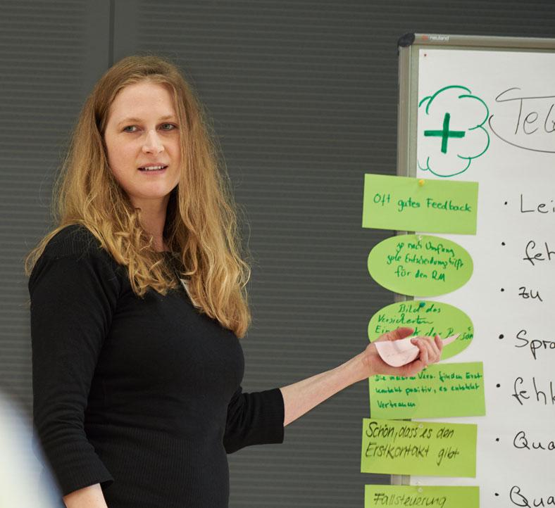 Das Foto zeigt eine Teilnehmerin während des Reha-Forums. Sie steht neben einem Flipchart, auf dem grüne Karten angepinnt sind.