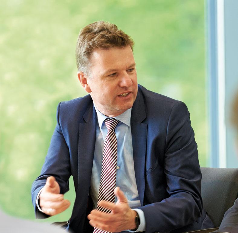 Das Foto zeigt einen Mann mit blauer Anzugjacke (Jörg Botti, Mitglied der Geschäftsführung der BG ETEM). Er gestikuliert mit beiden Händen. Im Vordergrund ist eine männliche Person schemenhaft zu erkennen.