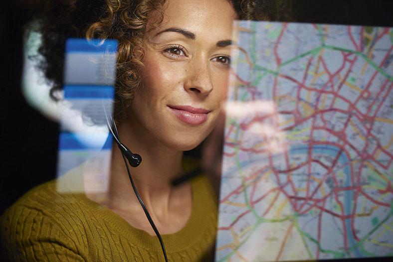 Dieses Foto zeigt eine Frau mit Headphones. Im Hintergrund eine Landkarte im Schaltzentrum einer Fuhrparkverwaltung.