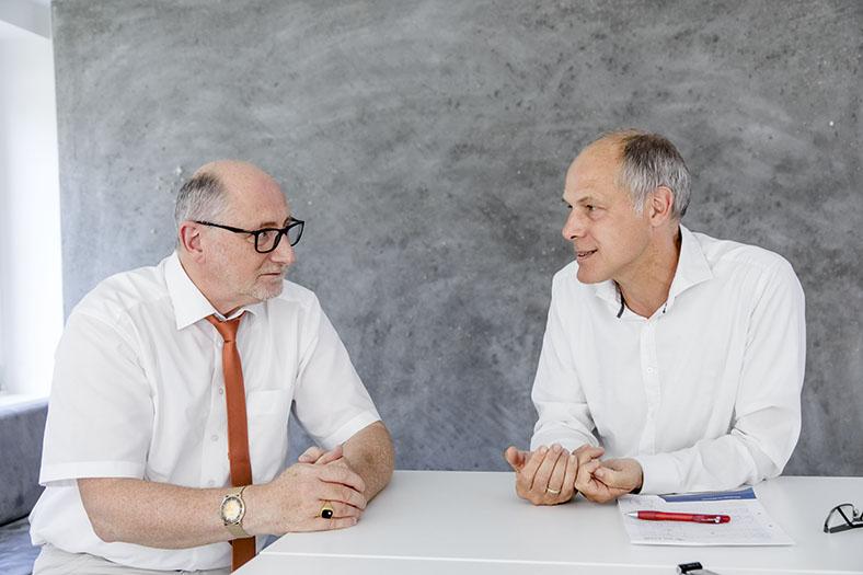 Auf diesem Bild sehen wir Dr. Ronald Unger (links) an einem Tisch mit Dr. Just Mields (rechts) während eines Gesprächs.