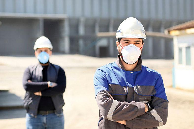 Auf dem Bild stehen zwei Arbeiter mit weißen Schutzhelmen in der Sonne vor einem Firmengebäude, einer links im Vordergrund, der andere unscharf rechts im Hintergrund. Beide tragen FFP2-Atemschutzmasken und haben die Arme vor der Brust verschränkt.