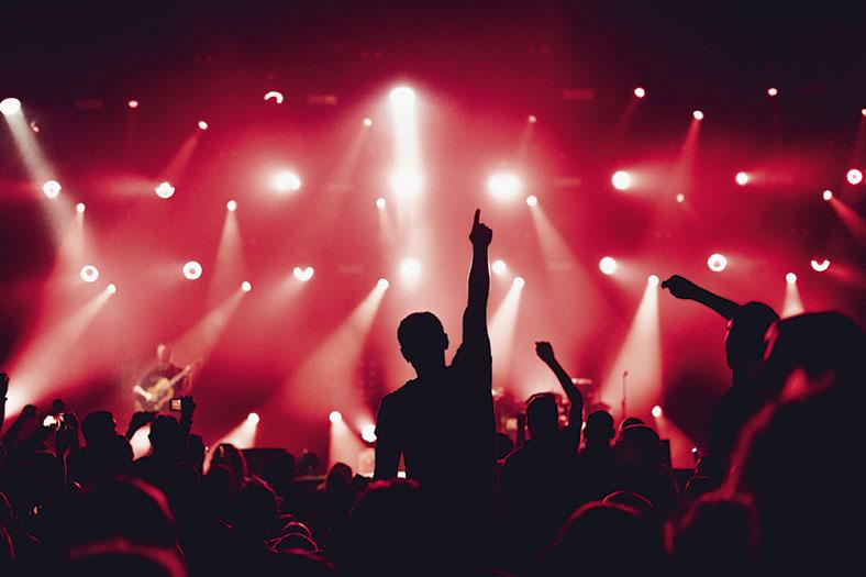 Auf dem Bild ist im Vordergrund eine Menschenmenge im Schatten zu sehen, die in den Hintergrund auf eine Bühne schauen, mehrere Personen strecken Arme in die Höhe. Im rot beleuchteten Hintergrund sieht man eine Bühne in rotes Licht getaucht sowie weiße Lichtkegel von mehreren Scheinwerfern. Auf der Bühne ist ein Mann mit einer Gitarre zu erkennen.