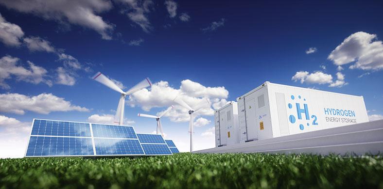"""Auf dem Foto sieht man links drei Sonnenkollektoren, mittig dahinter drei Windräder mir rotierenden Blättern und rechts zwei weiße Container mit der Aufschrift """"H2"""". Im Hintergrund ein tiefblauer Himmer mit einzelnen Wölkchen, ganz vorne ein Streifen grünes Gras."""