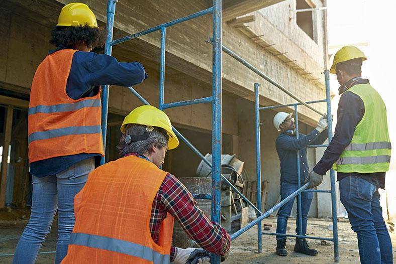 Das Bild zeigt mehrere Bauarbeiter mit Schutzhelmen, teilweise in orangen oder gelben Warnwesten, die ein blaues Stahlgestänge zusammenbauen. Im Hintergrund eine Baustelle mit einem Gebäude im Rohbauzustand.
