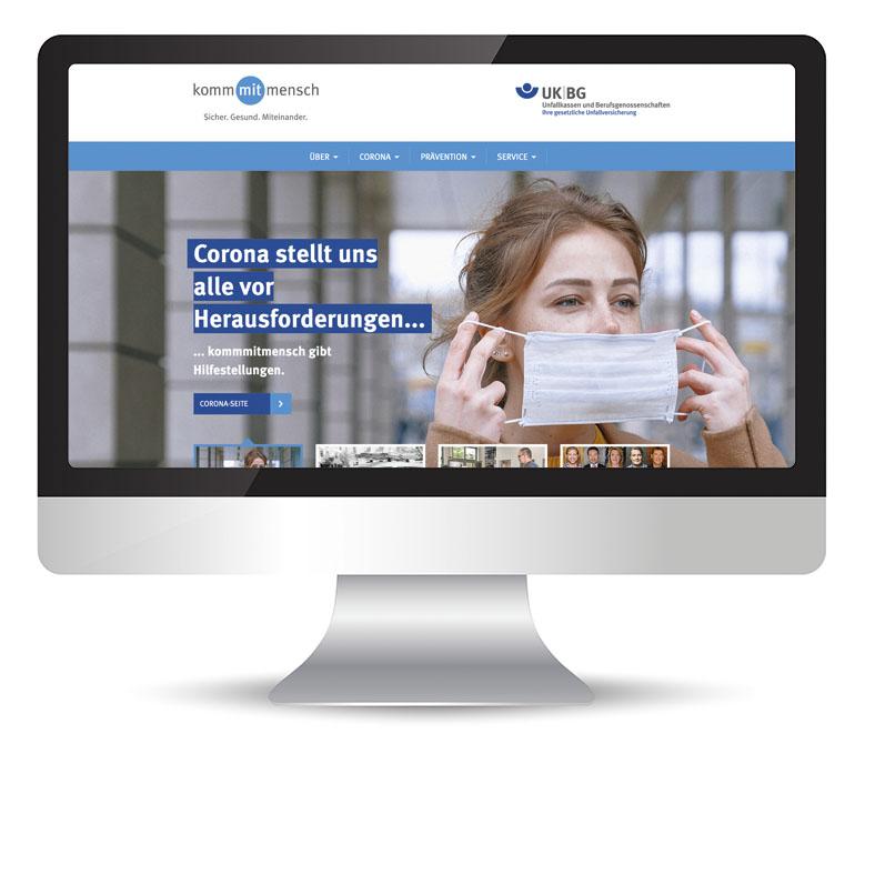 """Die Abbildung zeigt den Umriss eines Computermonitors, auf dem Bildschirm ist die Startseite von www.kommmitmensch.de zu sehen mit einer jungen Frau, die sich mit beiden Händen einen Mund-Nasen-Schutz an- oder auszieht. Links daneben steht """"Corona stellt uns alle vor Herausforderungen ...""""."""
