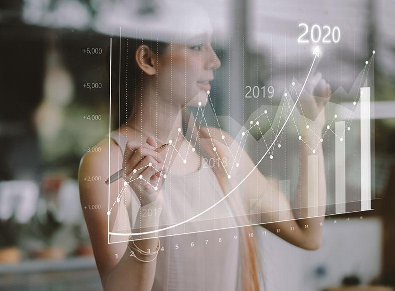 Auf dem Bild ist eine junge Frau mit dunklen Haaren zu sehen mit einem Stift in der Hand. Sie hat beide Hände sind auf eine vor ihr hängende, transparente Tafel gerichtet, auf der in weiß mehrere Verlaufskurven und Balkendiagramme mit den Jahreszahlen 2019 und 2020 aufgezeichnet sind.