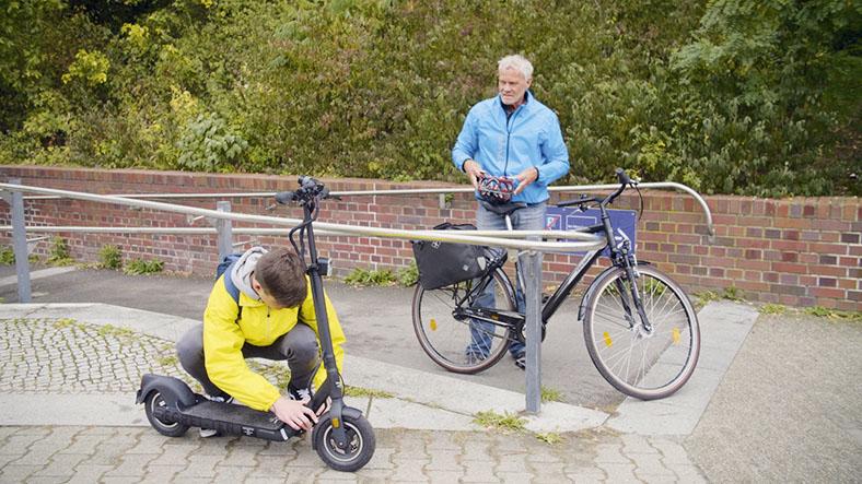 Ein Junge untersucht einen E-Scooter. Ein älterer Mann steht mit einem Fahrrad daneben.