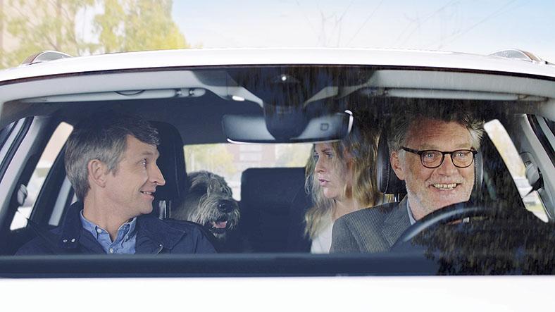 Drei Personen und ein Hund sitzen in einem Auto.